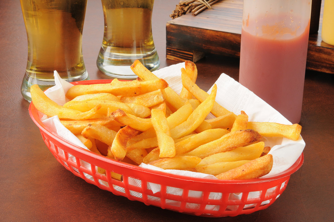 A basket of french fries and two tall glasses of beer